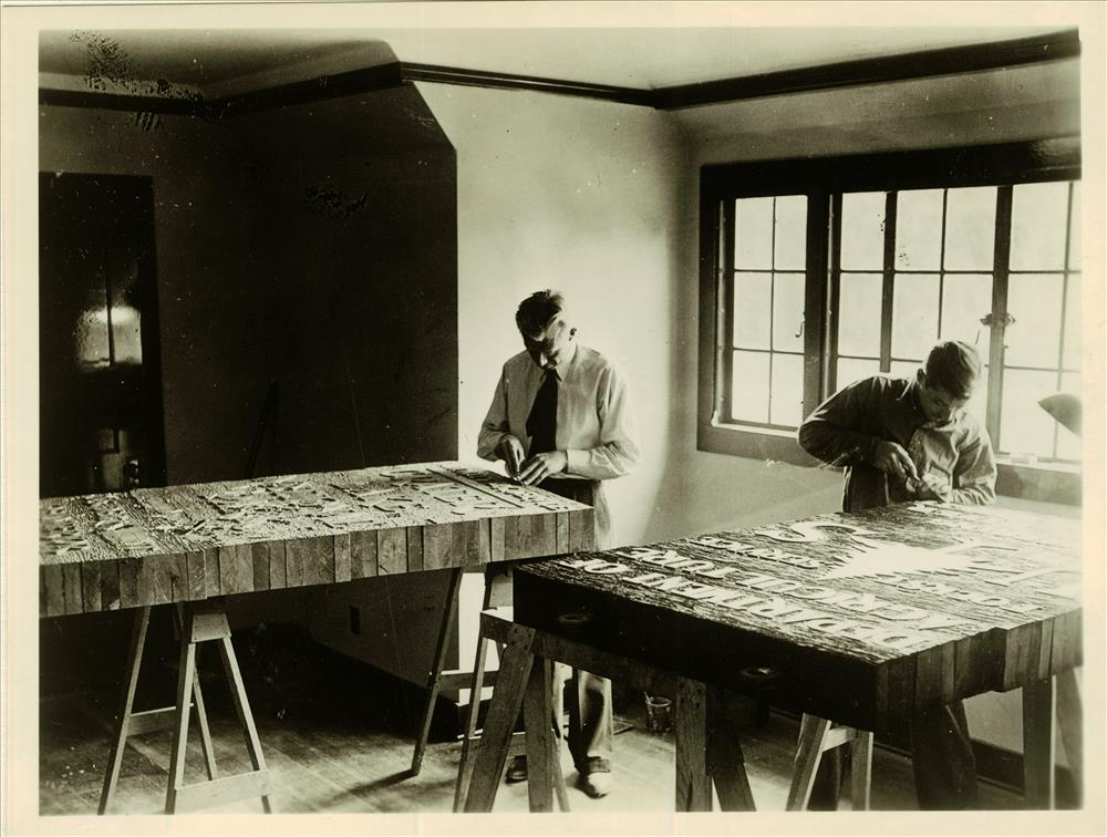 Carving Letters on Redwood Slabs. Upstairs room on West end of Ad. Building in Crater Lake NP, Nov 1936 probably Lange photo - Lange is on left