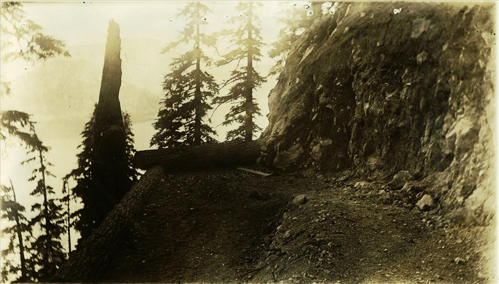 Crater Wall Trail headed below the Rim Village Cafeteria Cafe from about 1928 to 1959; switchback going looking down grade; log walls; obscured view of Wizard Island and lake