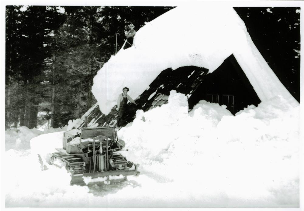 Crew with a bulldozer clearing snow from the roof of a building in Crater Lake NP, circa 1931-1932