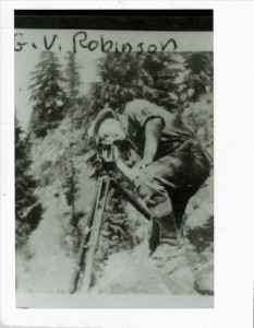 G. V. Robinson and transit, The road runs here. Crater Lake NP, 1918