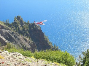 Helicopter with grappling hook attached close to caldera wall picking up loose pieces of debris from car wreck. 2010