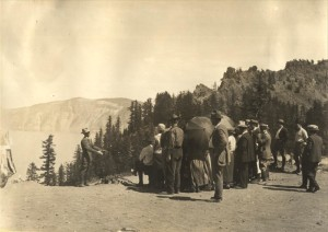 Naturalist (Interpretive) Ranger on caldera rim speaking to a group of visitors; view of lake and Garfield Peak in background 1935