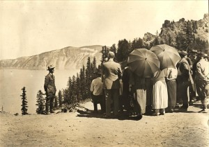 Naturalist Ranger, hands behind back, on caldera rim speaking to a group of visitors; view of lake and Garfield Peak in background 1935