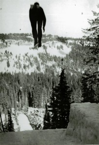 Ski jumper taking flight just north of Park Headquarters, Cascade Divide in distance, in Crater Lake NP, circa 1931-1932