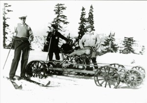 Two skiers and a partially uniformed ranger next to Ike Davidson's snow machine in Crater Lake NP, circa 1931-1932