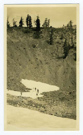 "Crater in Wizard Island, 90 ft. Deep, Snowballing in Aug., historic photograph Black and white print, 1921 5 1/4 x 3 1/4 inches This digital image is a scan of a black and white print. The original print is located in the Crater Lake Institute's collection of historical artifacts. The back of the print reads, ""Printed in Artura, Ransford 312-13 Stock Ex. Portland, Ore."" and (handwritten), ""Crater in Wizard Island, 90 ft deep - Snowballing in Aug"""
